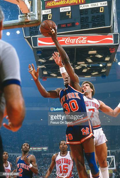 Bernard King of the New York Knicks lays the ball up in front of Kelly Tripucka of the Detroit Pistons during an NBA basketball game circa 1982 at...