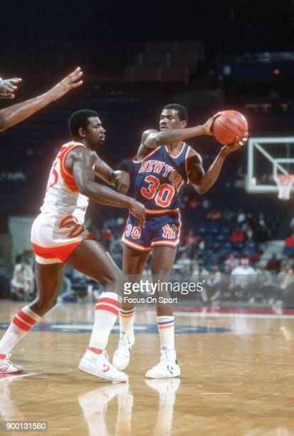 Bernard King of the New York Knicks looks to pass the ball over Antoine Carr of the Atlanta Hawks during an NBA basketball game circa 1984 at the...