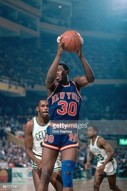 Bernard King of the New York Knicks rebounds against the Boston Celtics during a game played in 1984 at the Boston Garden in Boston Massachusetts...