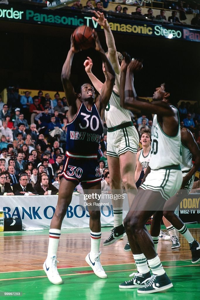 Bernard King #30 of the New York Knicks shoots against Larry Bird #33 and Robert Parish #00 of the Boston Celtics during a game played in 1983 at the Boston Garden in Boston, Massachusetts.