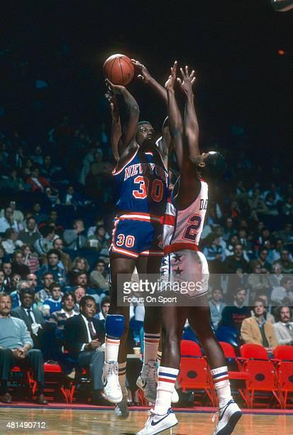 Bernard King of the New York Knicks shoots over Charles Davis of the Washington Bullets during an NBA basketball game circa 1984 at the Capital...