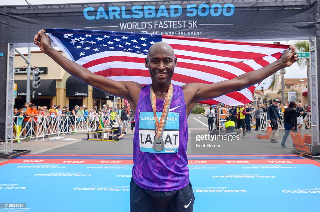 Bernard Lagat of the USA poses at the finish line after setting the new men's Masters world record for road race on April 3, 2016 in Carlsbad, California.