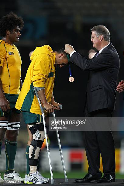 Bernard Lapasset Chairman of the IRB award an injured Quade Cooper of the Wallabies his bronze medal after the 2011 IRB Rugby World Cup bronze final...