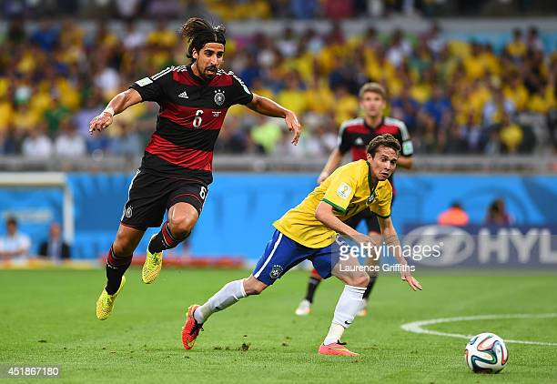 Bernard of Brazil is challenged by Sami Khedira of Germany during the 2014 FIFA World Cup Brazil Semi Final match between Brazil and Germany at...