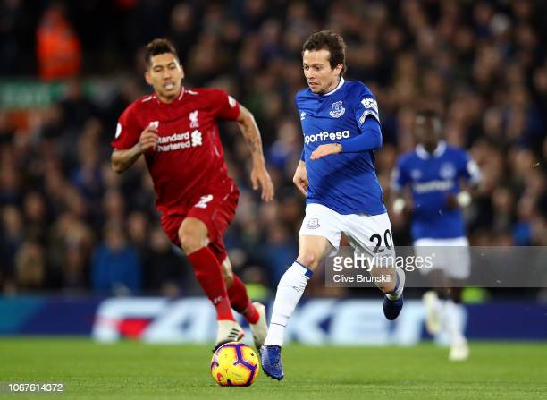 Bernard of Everton runs with the ball under pressure from Roberto Firmino of Liverpool during the Premier League match between Liverpool FC and...