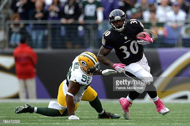 Bernard Pierce of the Baltimore Ravens avoids the tackle of Mike Neal of the Green Bay Packers in the first half during a game at MT Bank Stadium on...