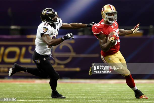 Bernard Pollard of the Baltimore Ravens tries to tackle Vernon Davis of the San Francisco 49ers after a catch in the first half during Super Bowl...