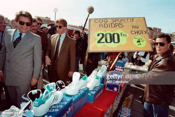 Bernard Tapie watches the Adidas shoes in market of Plan de Cuques during the regional elections campaign on March 16 1992 / AFP PHOTO / Georges GOBET