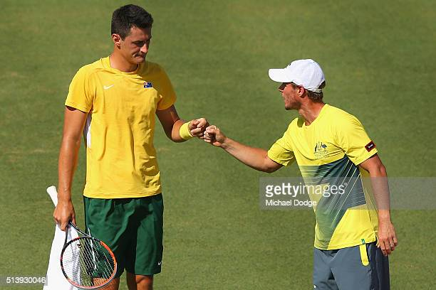 Bernard Tomic of Australia celebrates a game Captain Lleyton Hewitt in his match against John Isner of the USA during the Davis Cup tie between...
