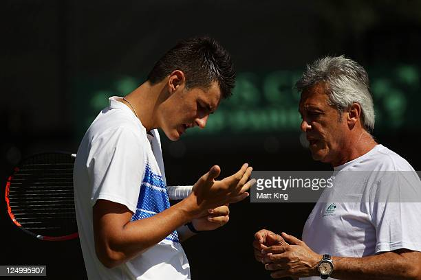 Bernard Tomic of Australia inspects his injured hand during a practice session ahead of the Davis Cup World Group Playoff Tie between Australia and...