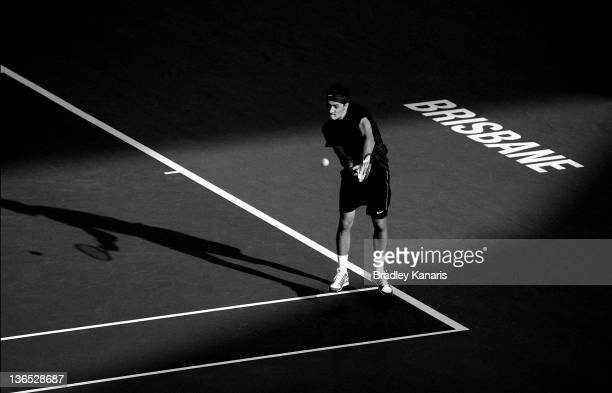 Bernard Tomic of Australia plays a backhand against Andy Murray of Great Britain in their semi-final match during day seven of the 2012 Brisbane...