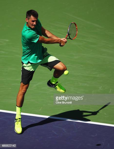 Bernard Tomic of Australia plays a backhand against Bjorn Fratangelo of the United States in their first round match during day four of the BNP...