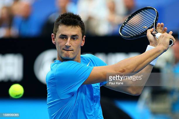 Bernard Tomic of Australia plays a backhand in his singles match against Andreas Seppi of Italy during day six of the Hopman Cup at Perth Arena on...