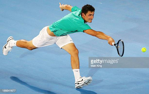 Bernard Tomic of Australia plays a backhand in the men's final match against Kevin Anderson of South Africa during day seven of the Sydney...
