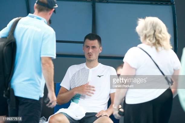 Bernard Tomic of Australia receives medical attention in his match against Denis Kudla of the USA during 2020 Australian Open Qualifying at Melbourne...