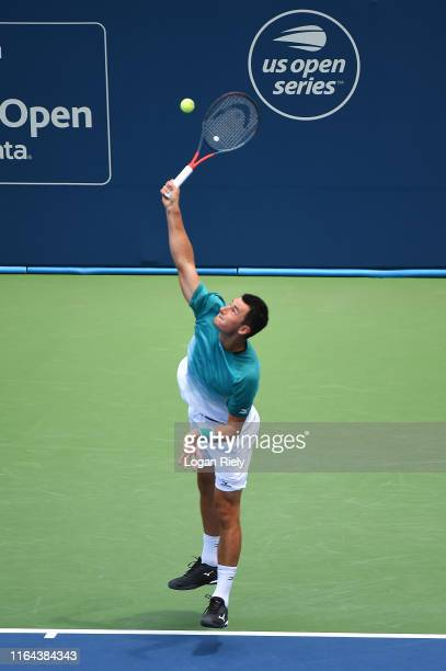 Bernard Tomic of Australia serves to Alex De Minaur of Australia during the BB&T Atlanta Open at Atlantic Station on July 26, 2019 in Atlanta,...