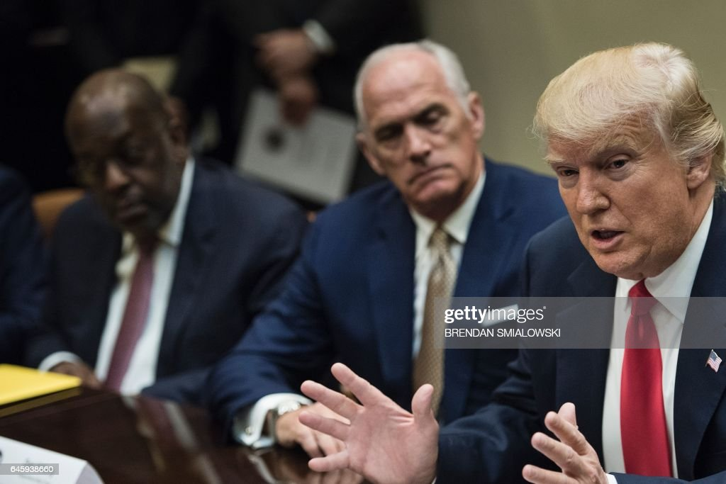 Bernard Tyson (L), CEO of Kaiser Permanente, Daniel J. Hilferty (C), President and CEO of of Independence Blue Cross listen while US President Donald Trump speaks before a meeting with health insurance executives in the Roosevelt Room of the White House February 27, 2017 in Washington, DC. / AFP / Brendan Smialowski