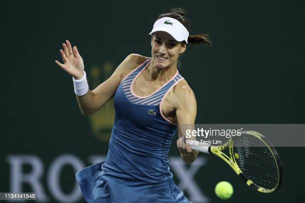 Bernarda Pera of the United States plays a forehand against Catherine McNally of the United States during their ladies singles first round match on...