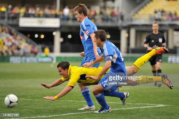 Bernardo Anor of the Columbus Crew is upended as he tries to split the defense of Davy Arnaud and Justin Braun of the Montreal Impact in the second...