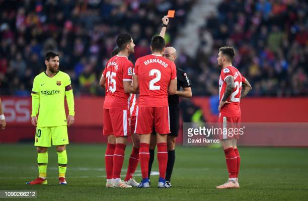 Bernardo Espinosa of Girona is shown a red card by referee Gonzalez Fuertes as Juanpe of Girona protests and Lionel Messi of Barcelona looks on...
