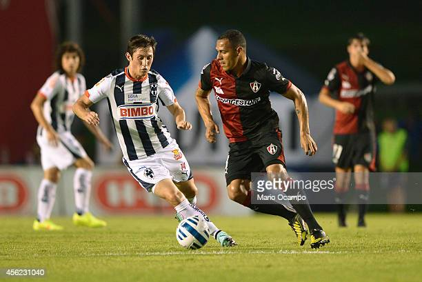 Bernardo Hernandez of Monterrey fights drives the ball as Aldo Leao of Atlas tries to defend during a match between Monterrey and Atlas as part of...