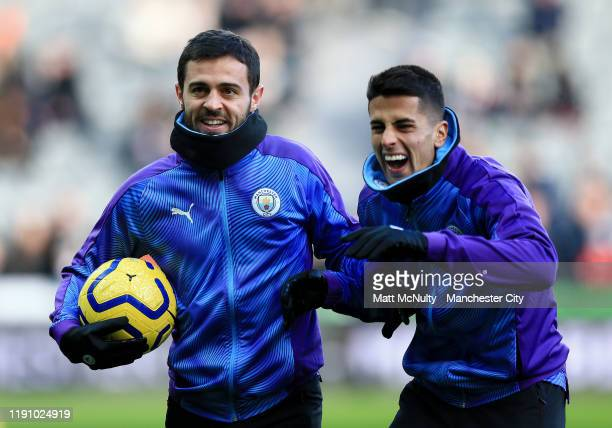 Bernardo Silva and Joao Cancelo of Manchester City laugh in the warm up prior to during the Premier League match between Newcastle United and...