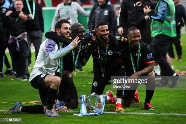 Bernardo Silva Benjamin Mendy Riyad Mahrez and Raheem Sterling of Manchester City celebrate with the trophy during the Carabao Cup Final between...