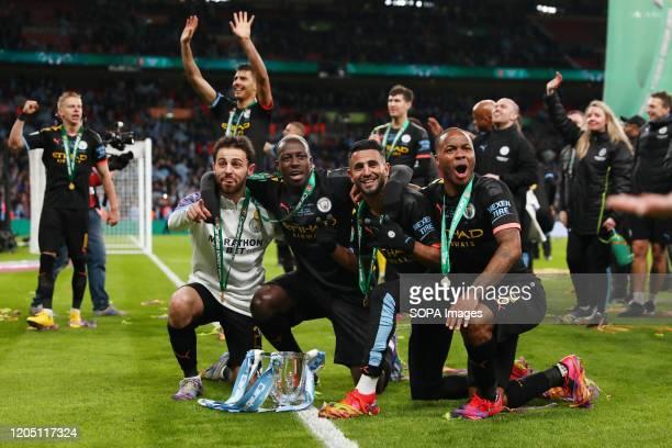 Bernardo Silva Benjamin Mendy Riyad Mahrez and Raheem Sterling of Manchester City celebrate with the trophy after the Carabao Cup Final match between...