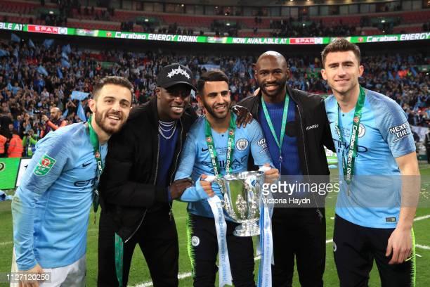 Bernardo Silva Benjamin Mendy Riyad Mahrez Eliaquim Mangala and Aymeric Laporte of Manchester City celebrate victory with the trophy after the...