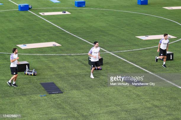 Bernardo Silva Ilkay Gundogan and David Silva of Manchester City warm up during the training session at Manchester City Football Academy on June 01...
