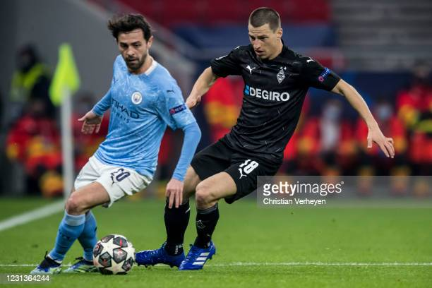 Bernardo Silva of Manchester City and Stefan Lainer of Borussia Moenchengladbach battle for the ball during the UEFA Champions League Round Of 16 Leg...