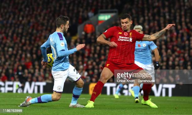 Bernardo Silva of Manchester City and Trent AlexanderArnold of Liverpool handle the ball during the Premier League match between Liverpool FC and...