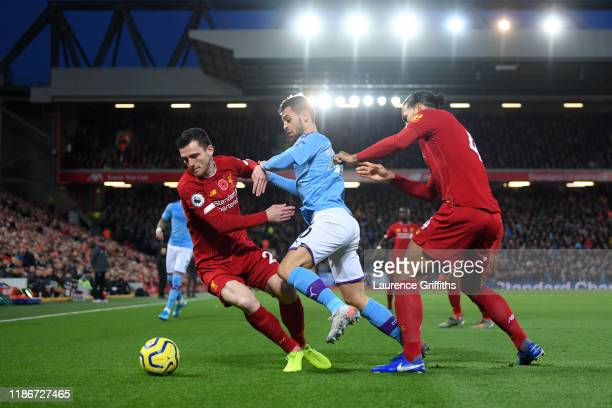 Bernardo Silva of Manchester City battles for possession with Virgil van Dijk and Andy Robertson of Liverpool during the Premier League match between...