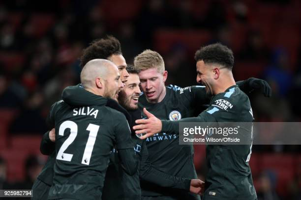 Bernardo Silva of Manchester City celebrates scoring the opening goal among team mates during the Premier League match between Arsenal and Manchester...