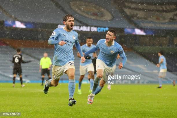 Bernardo Silva of Manchester City celebrates with Phil Foden after scoring their team's first goal during the Premier League match between Manchester...
