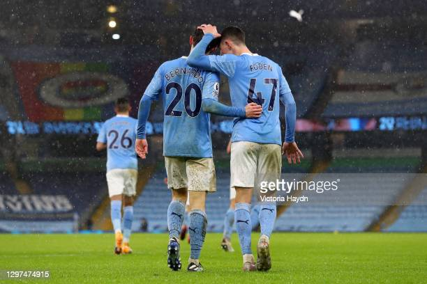 Bernardo Silva of Manchester City celebrates with team mate Phil Foden after scoring their side's first goal during the Premier League match between...