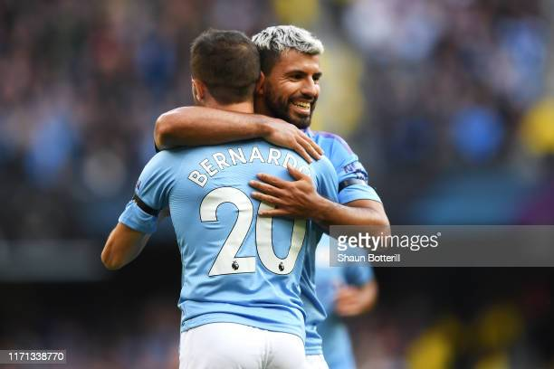 Bernardo Silva of Manchester City celebrates with teammate Sergio Aguero after scoring his team's fourth goal during the Premier League match between...