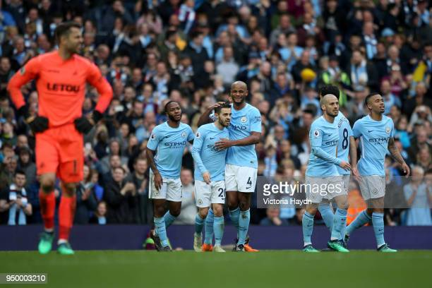 Bernardo Silva of Manchester City celebrates with Vincent Kompany after scoring his side's fourth goal during the Premier League match between...