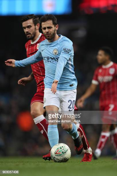 Bernardo Silva of Manchester City competes with Marlon Pack of Bristol City during the Carabao Cup SemiFinal first leg match between Manchester City...