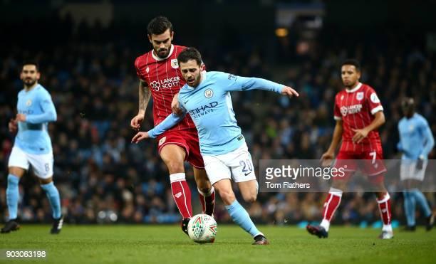 Bernardo Silva of Manchester City evades Marlon Pack of Bristol City during the Carabao Cup SemiFinal First Leg match between Manchester City and...