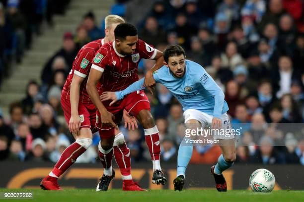 Bernardo Silva of Manchester City holds off Korey Smith of Bristol City during the Carabao Cup SemiFinal First Leg match between Manchester City and...