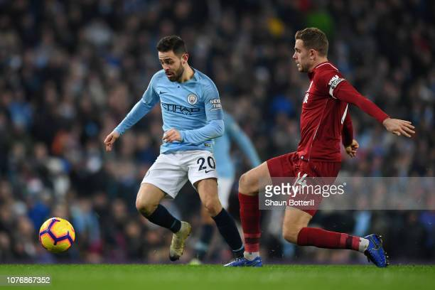 Bernardo Silva of Manchester City is challenged by Jordan Henderson of Liverpool during the Premier League match between Manchester City and...