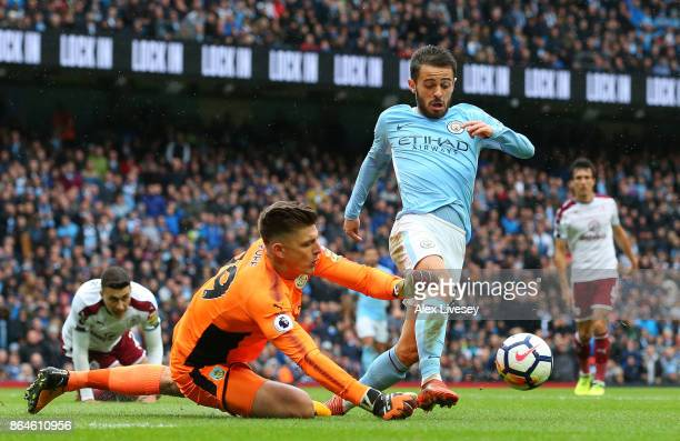 Bernardo Silva of Manchester City is challenged by Nick Pope of Burnley to concede a penalty during the Premier League match between Manchester City...