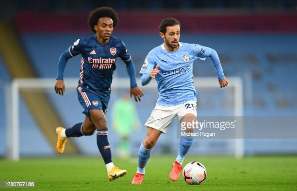 Bernardo Silva of Manchester City is challenged by Willian of Arsenal during the Premier League match between Manchester City and Arsenal at Etihad...