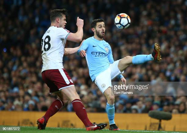 Bernardo Silva of Manchester City is tackled by Kevin Long of Burnley during the The Emirates FA Cup Third Round match between Manchester City and...