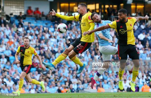 Bernardo Silva of Manchester City jumps with Jose Holebas and Adrian Mariappa of Watford during the Premier League match between Manchester City and...