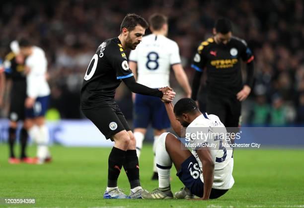 Bernardo Silva of Manchester City offers a hand to Japhet Tanganga of Tottenham Hotspur after the Premier League match between Tottenham Hotspur and...