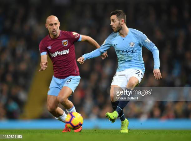 Bernardo Silva of Manchester City passes the ball under pressure from Pablo Zabaleta of West Ham United during the Premier League match between...