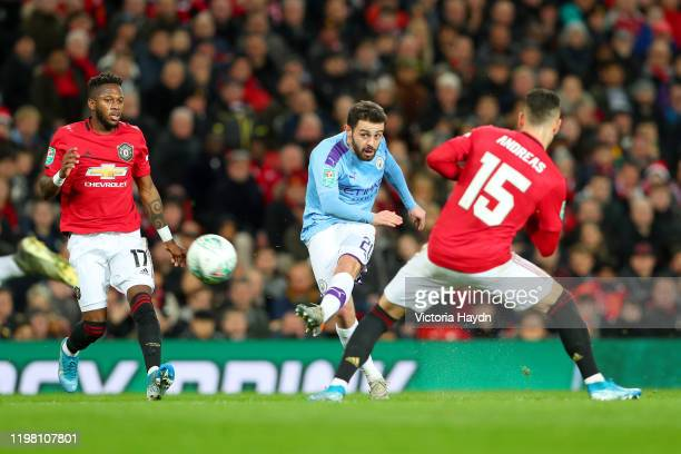 Bernardo Silva of Manchester City scores his team's first goal as Andreas Pereira of Manchester United attempts to block during the Carabao Cup Semi...
