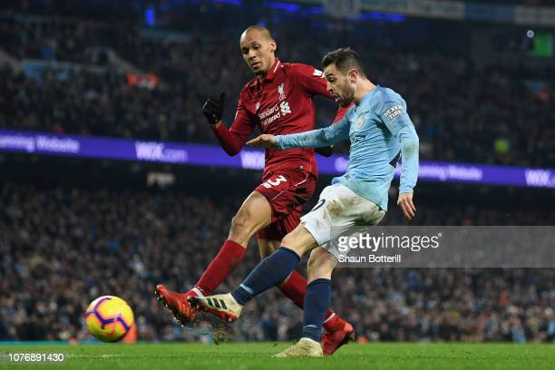 Bernardo Silva of Manchester City shoots as he is challenged by Fabinho of Liverpool during the Premier League match between Manchester City and...